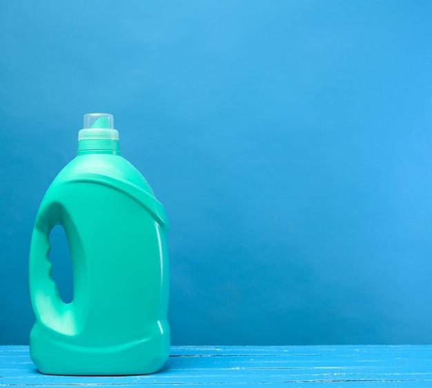Зеленая пластиковая бутылка с моющими средствами на синем фоне, копией пространства