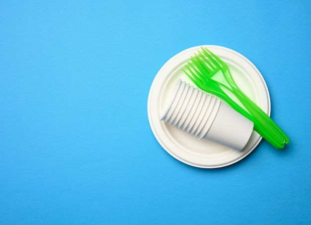 Green plastic forks and empty white paper disposable plates on a blue background, top view, set