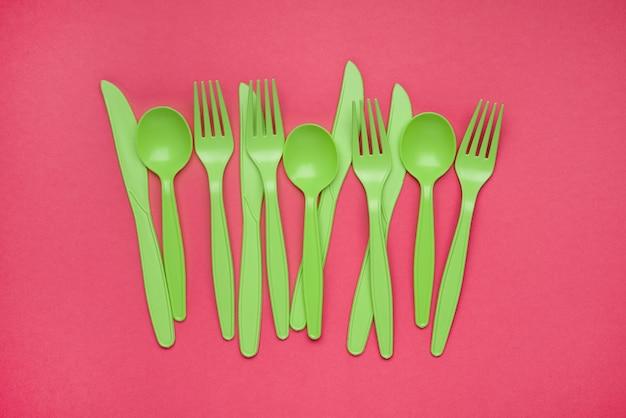ピンクの紙に緑色のプラスチックフォーク、スプーン、ナイフ。さまざまなスプーンフォークナイフと環境に優しいプラスチックコンセプトのプラスチックカトラリーのセット。フラットレイ。水平。クローズアップ上面図