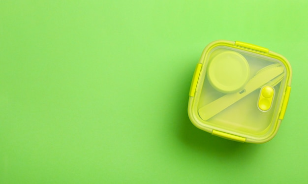 Green plastic lunch box on green background.top view,flat lay. food container for school and office.copy space.