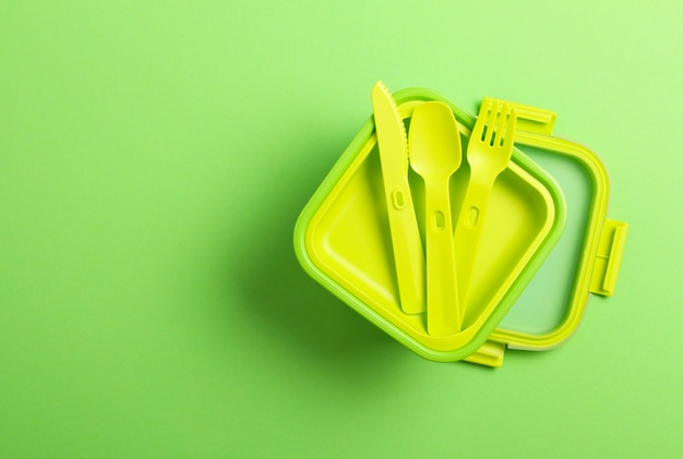 Green plastic lunch box with fork, spoon, knife on green background.top view,flat lay. food container for school and office.copy space.