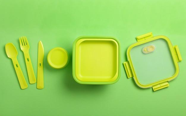 Зеленая пластичная коробка для завтрака с вилкой, ложкой, ножом на зеленой предпосылке взгляд сверху, плоское положение. контейнер для еды для школы и офиса.