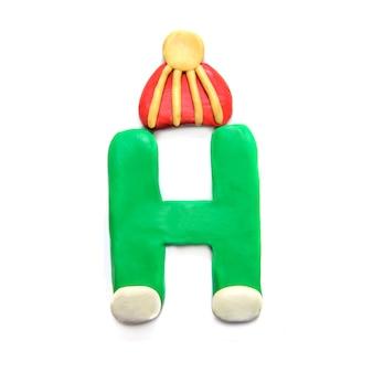 Зеленый пластилин буква h алфавит в зимней полосатой шляпе на белом фоне