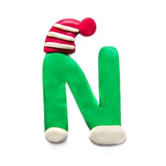 Зеленая пластилиновая буква n алфавит в зимней красной полосатой шапке на белом фоне