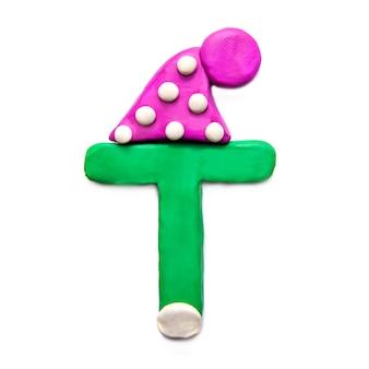 Зеленый пластилин буква t алфавит в зимней фиолетовой шляпе на белом фоне