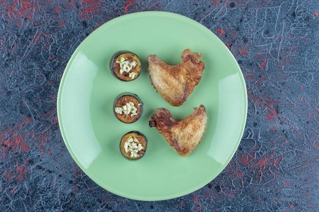 Un piatto verde di carne di pollo e melanzane a fette fritte.