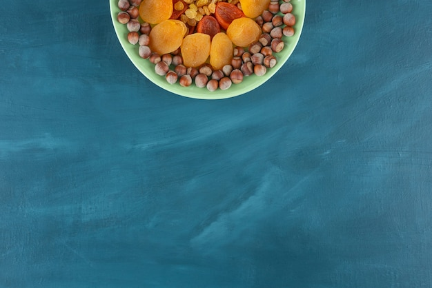 Green plate of dried fruits and hazelnuts on blue table.