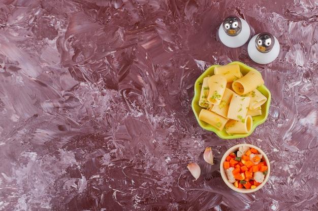 Un piatto verde di pasta cruda secca con insalata di verdure miste fresche e spezie.
