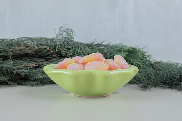 A green plate full of heart shaped jelly candies .