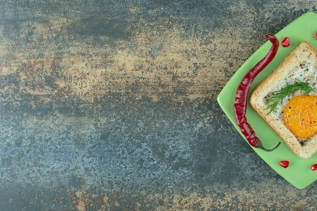 Un piatto verde pieno di frittata in pane bianco con pepe