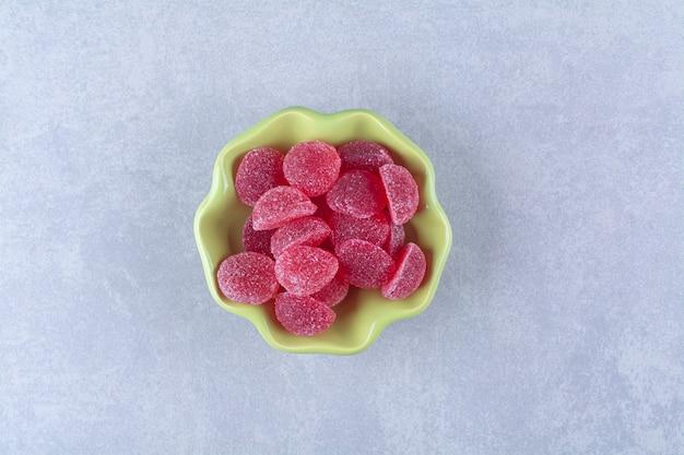 Un piatto verde pieno di caramelle di gelatina zuccherate sulla superficie grigia