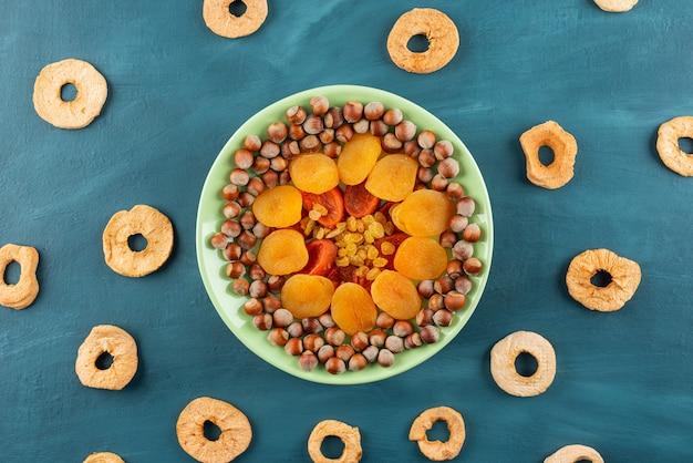 말린 과일과 헤이즐넛 블루 테이블에 녹색 접시.