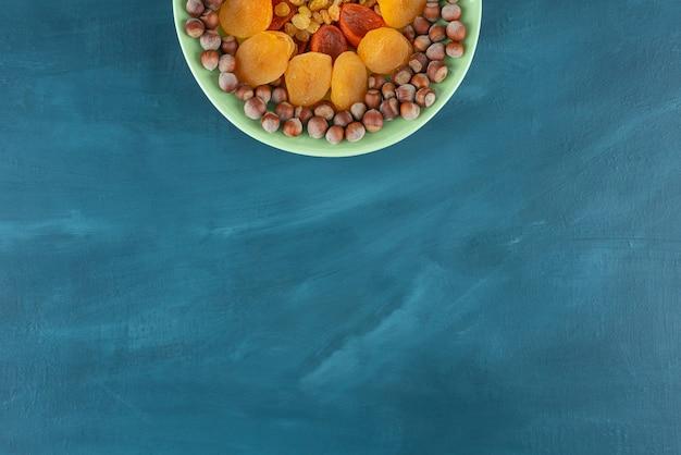 青いテーブルの上のドライフルーツとヘーゼルナッツの緑のプレート。