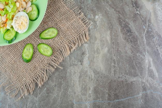 대리석 표면에 신선한 맛있는 샐러드의 녹색 접시.