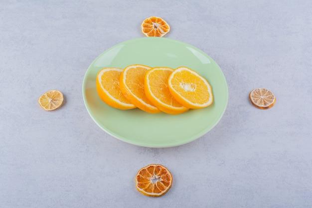 石のテーブルの上の新鮮なオレンジスライスの緑のプレート。