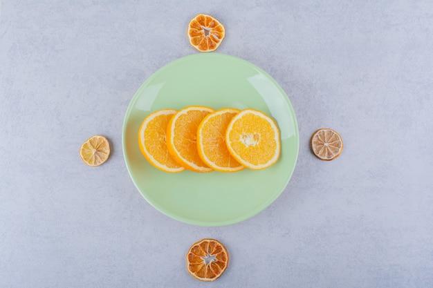 石の上の新鮮なオレンジスライスの緑のプレート。