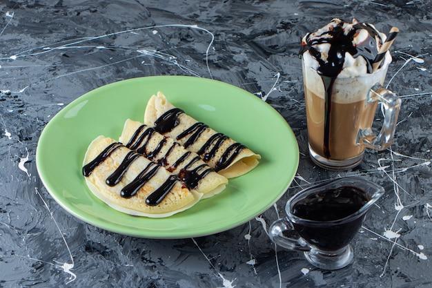 自家製クレープのグリーンプレートとチョコレートのトッピングとアイスコーヒーのグラス。