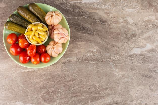 石のテーブルの上の漬物塩野菜の緑のプレート。
