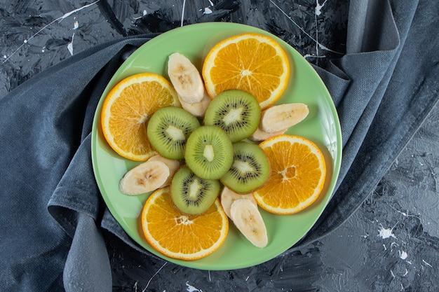 대리석 표면에 얇게 썬 오렌지, 키위, 바나나의 녹색 접시.