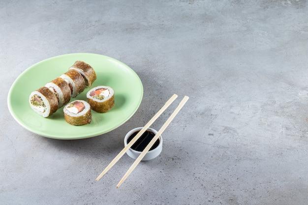 초밥의 녹색 접시 돌 배경에 참치와 롤.