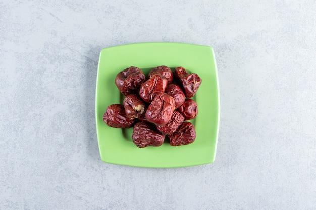 대리석 배경에 맛있는 익은 은베리의 녹색 접시.