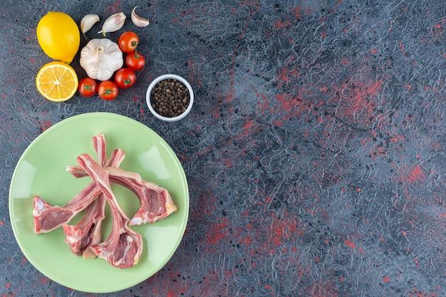 大理石の野菜と未調理の子羊の手足の緑のプレート。