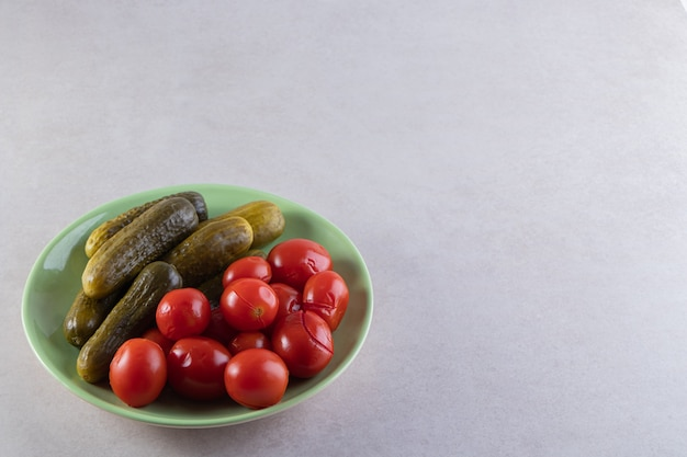 Green plate of pickled cucumbers and tomatoes on stone table.