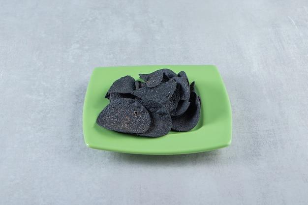 Piatto verde di patatine nere croccanti salate su pietra.