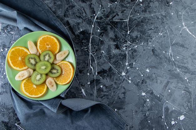 Green plate of sliced orange, kiwi and banana on marble surface.