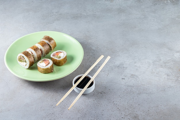 Green plate of sushi rolls with tuna fish on stone background.