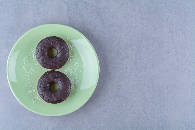 A green plate of two fresh chocolate doughnuts with sugar powder.