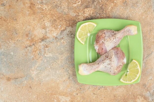 Un piatto verde di cosce di pollo crude con fette di limone