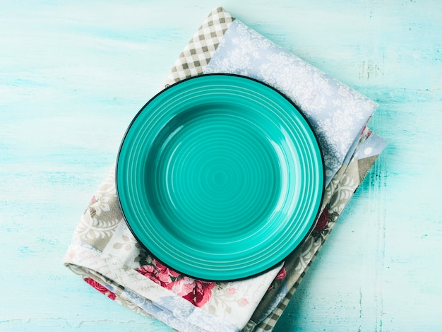 Green plate on vintage napkin wooden textured