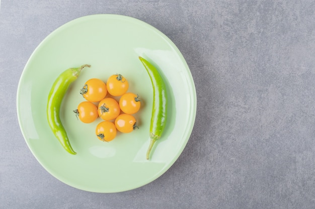 A green plate with cherry yellow tomatoes and chili peppers