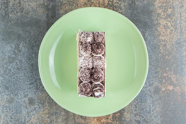 Un piatto verde con un pezzo di torta in polvere di cacao