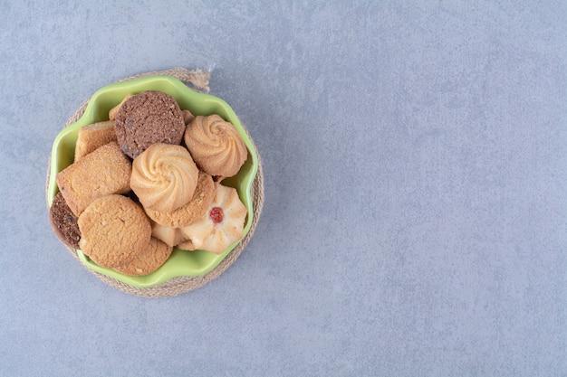 Un piatto verde con deliziosi biscotti rotondi dolci su tela di sacco.