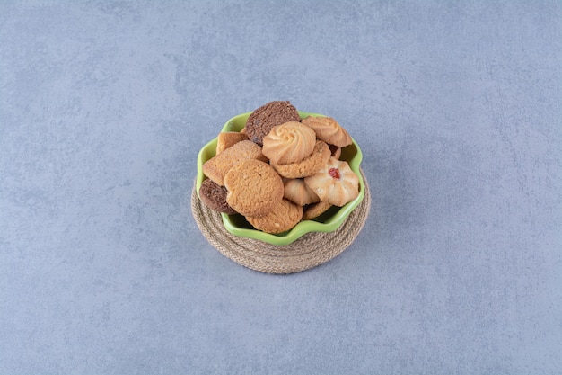 A green plate with sweet round delicious cookies on sackcloth