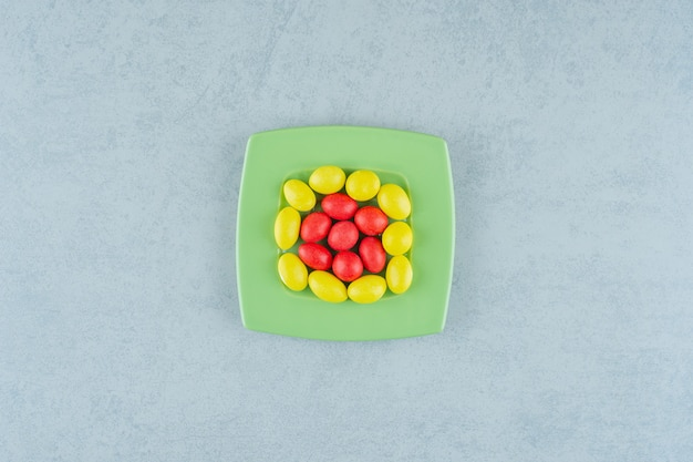 A green plate with sweet yellow and red candies on white background . high quality photo