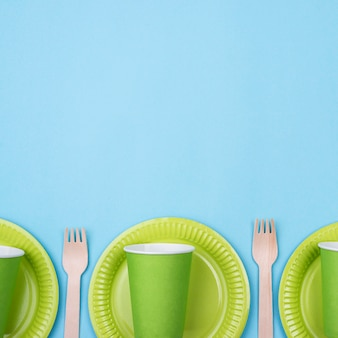 Green plates with cups and cutlery copy space