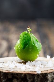 Green plum with leaves and salt crystals on wooden and wooden piece wall, side view.