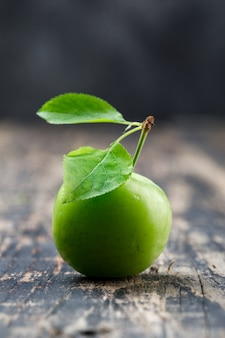Green plum with leaves on wooden and grungy wall, side view.