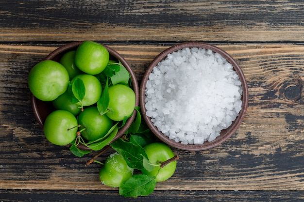 Green plums in a clay plate with salt in bowl and leaves flat lay on a wooden wall