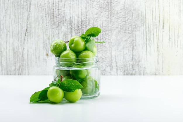 Зеленые сливы в мини-банке с листьями сбоку на белой и шероховатой стене