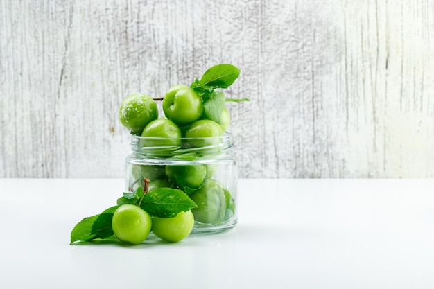 Green plums in a mini jar with leaves side view on white and grungy wall