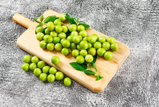 Green plums with leaves in a cutting board on grungy grey. high angle view.