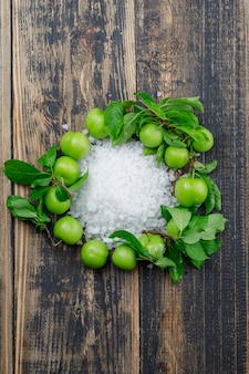 Green plums with salt crystals, leaves top view on a wooden wall