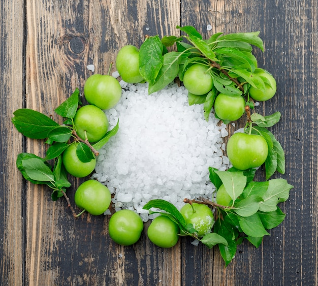 Prugne verdi con cristalli di sale, foglie sulla parete di legno, piatto disteso.