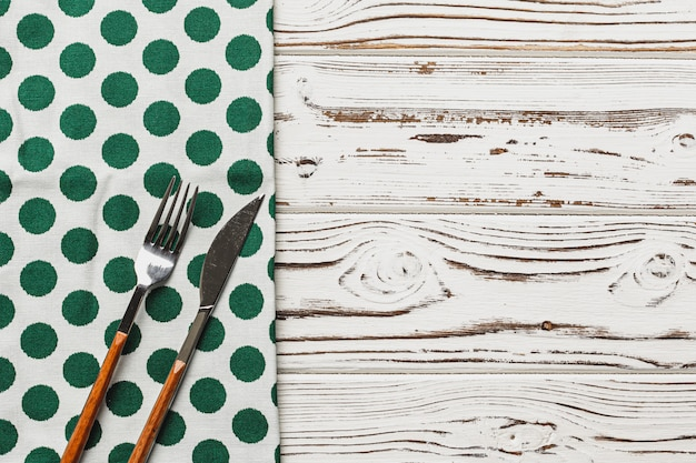 Green polka dot napkin on weathered wooden background, copy space