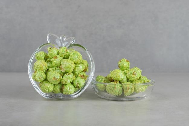 Popcorn verde riempito in un porta caramelle a forma di mela su fondo di marmo.