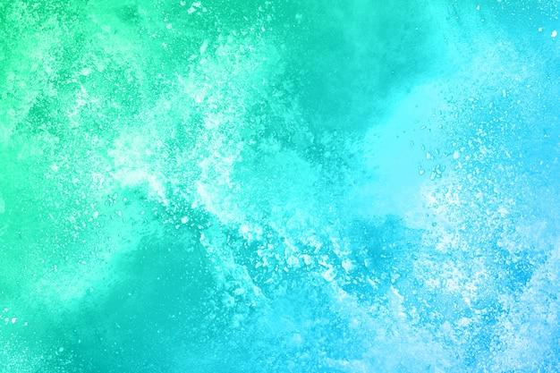 白い背景の上の緑の粉の爆発